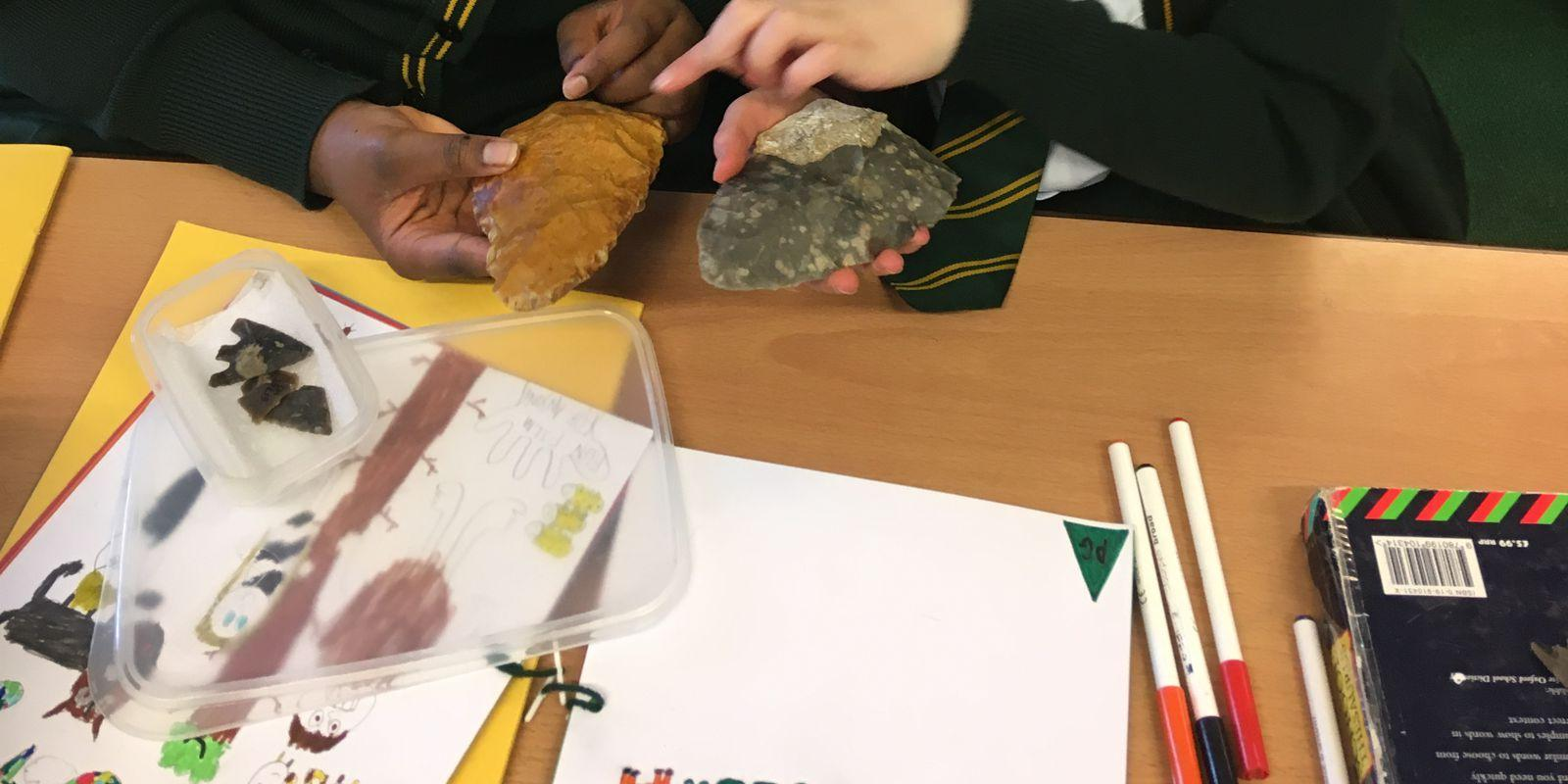 Pupils from St James' C of E Primary School studying a palaeolithic handaxe and a replica