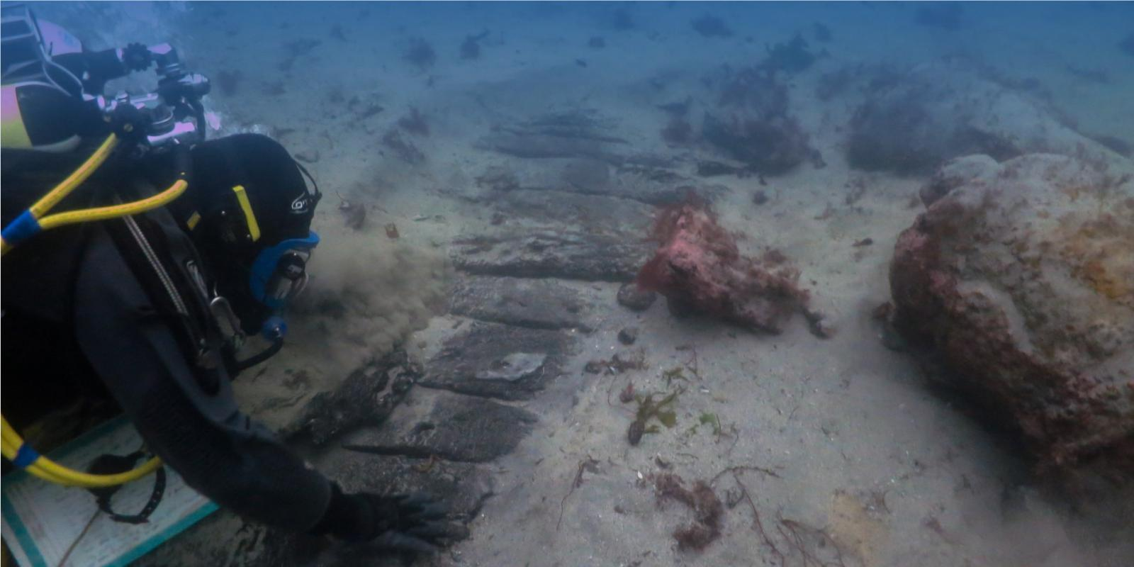Diver investigating a wreck on the seabed