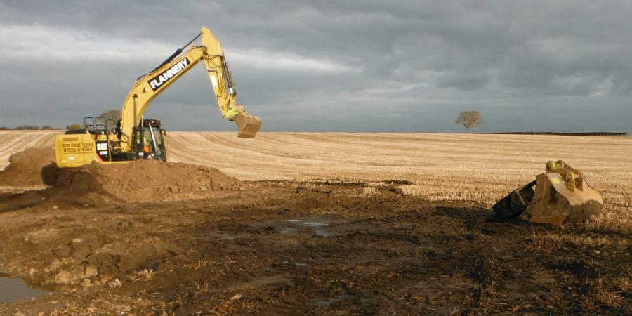A digger excavating in a field