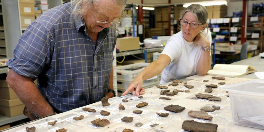 Phil Harding being shown pottery mould fragments in the finds room