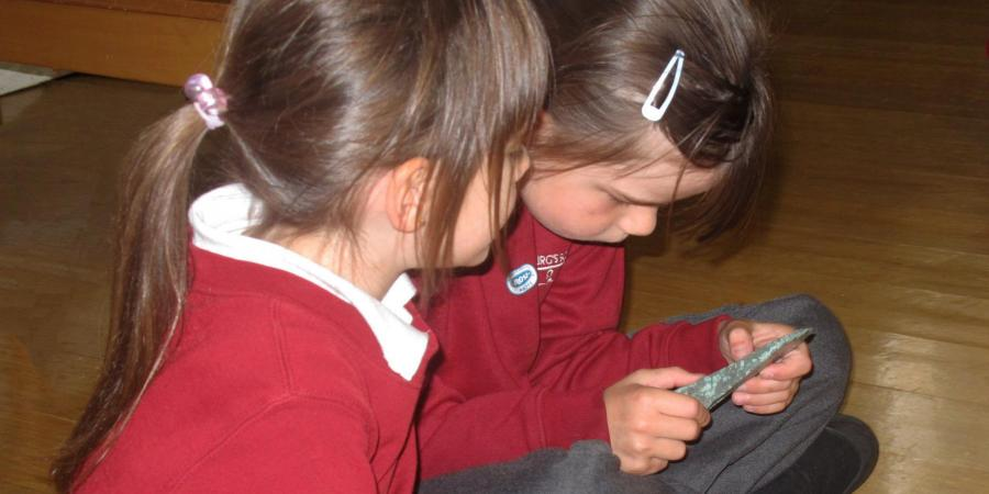 Children examining a bronze age palstave (axe head)