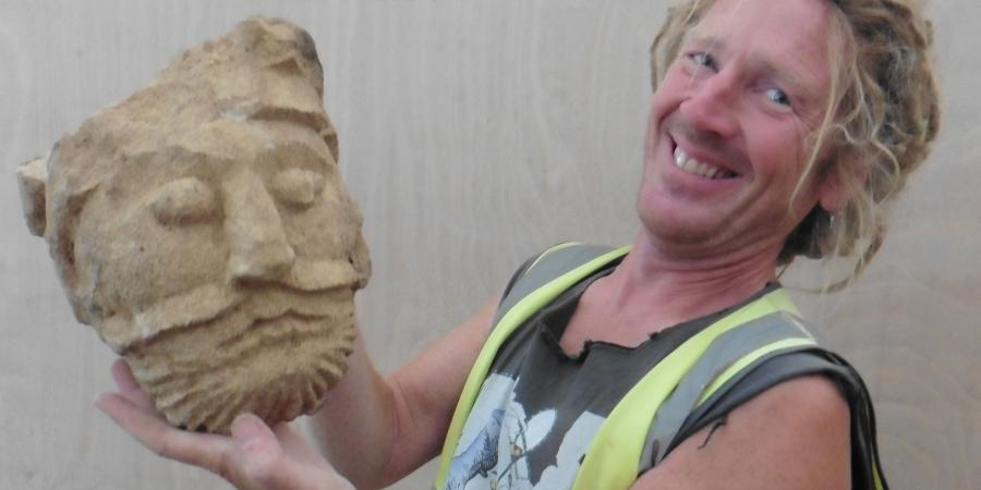 Archaeologist Lee Newton with the carved head