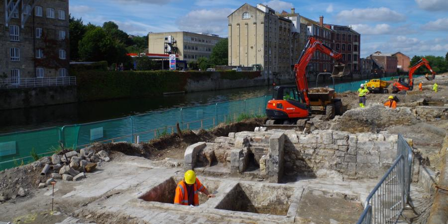 Archaeological excavation underway with historic building behind