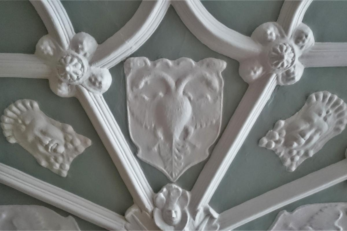 Detail of escutcheons and masks on the ceiling at The Grapes