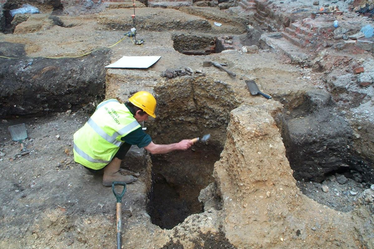 Excavating a medieval pit which cut through the lighter gravel of a Roman road at Fenchurch