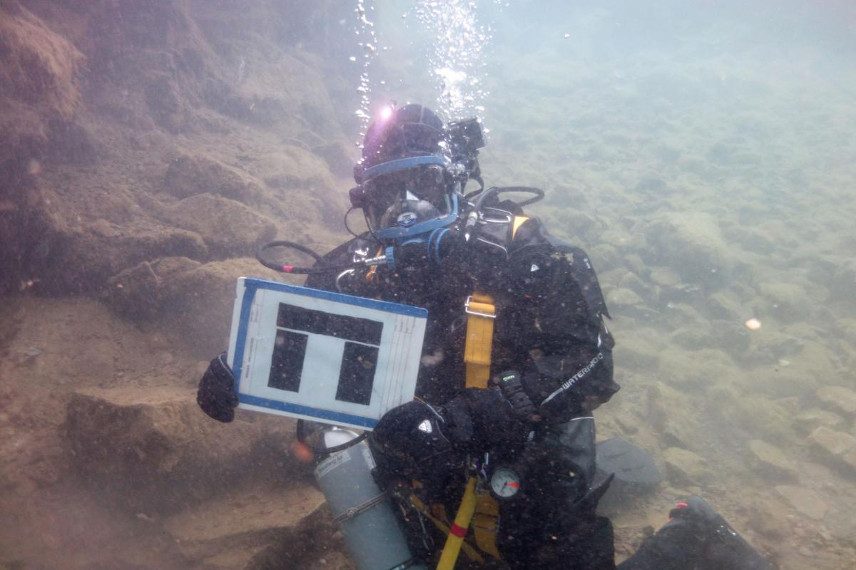 A diver holding the Wessex Archaeology logo