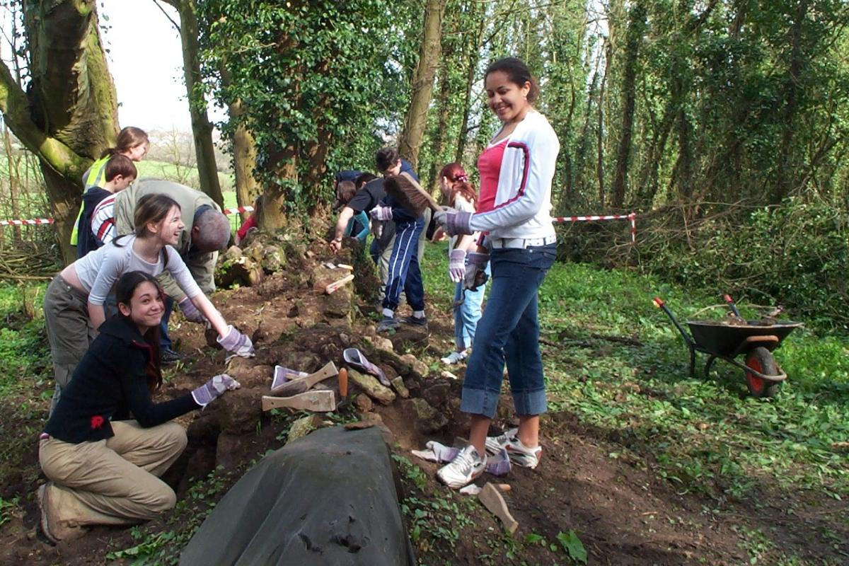 Young volunteers help to clear an old wall during the restoration work