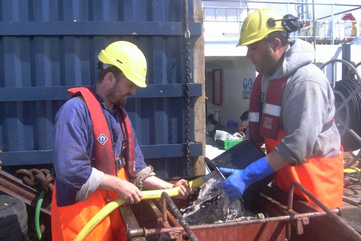 Retained archaeologists seiving marine sediments