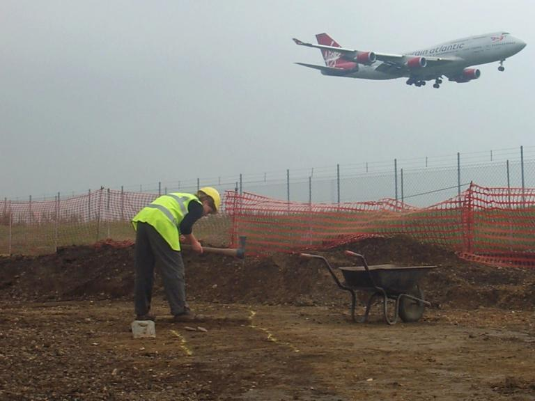 Aircraft landing at Heathrow Airport behind an archaeologist digging